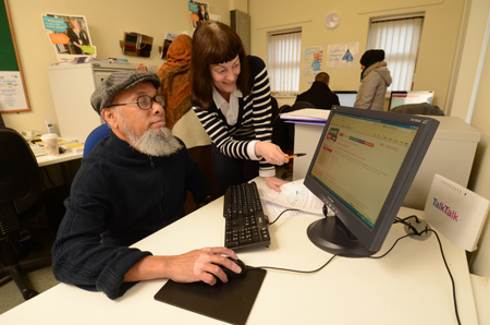 Man at computer with lady helping him